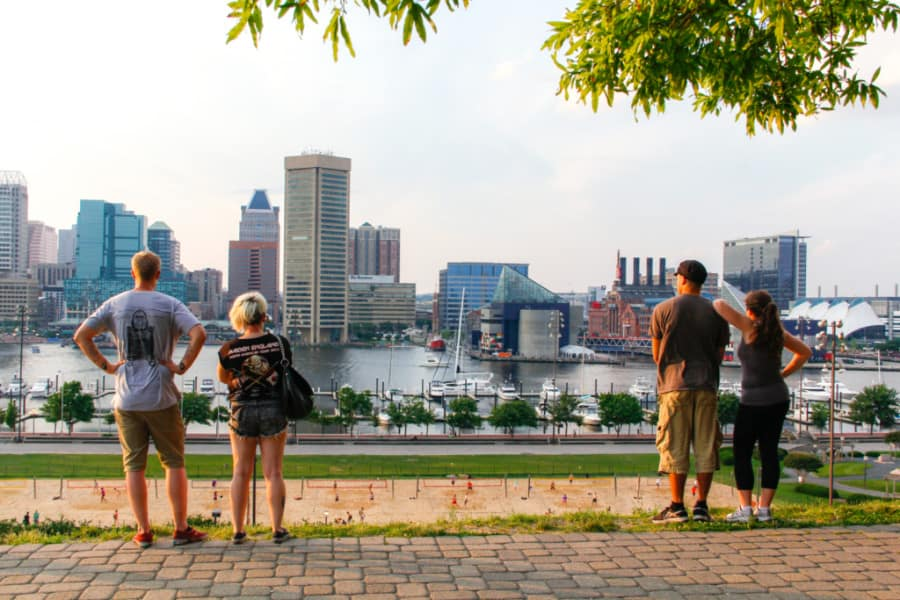 Two couples stand, looking at the Inner Harbor and skyline of Baltimore.